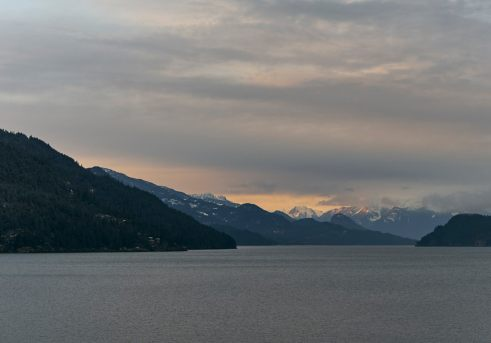 Moody image of Harrison Lake with sunset hitting the snow covered mountain ranges in the distance