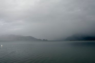 Moody image of Harrison Lake with snow flurries crossing the water and clouds enveloping the mountain ranges