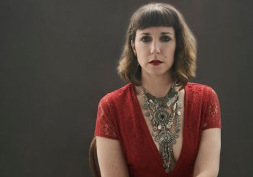 Portrait of a woman in a red lace dress with stacked silver necklaces and red lipstick