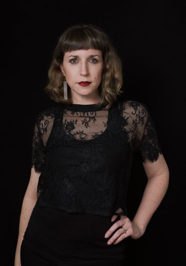 Portrait of a woman in a black lace top with red lipstick looking the camera on a black background