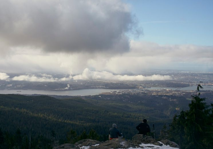 Image of 2 people sitting on rocks in the foreground looking across the Vancouver skyline from the top of Dog Mountain on a partly cloudy day