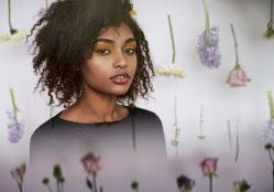 Portrait of a young woman with natural hair sitting in front of a wall of hanging spring blooms
