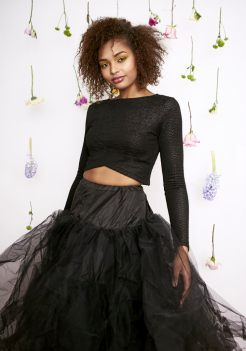 Portrait of a young woman with natural hair standing and smiling holding her tutu skirt in front of a wall of hanging spring blooms