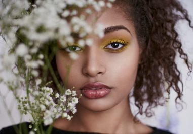 Portrait of a young woman with natural hair and bold eye make up looking at the camera through baby's breath flowers