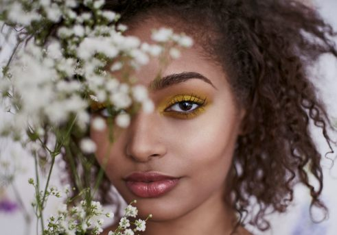 Portrait of a young woman with natural hair and bold eye make up smiling at the camera through baby's breath flowers