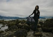 Outdoor natural light portrait of a woman on a rock shoreline on a moody cloudy day, wearing a billowing chiffon skirt and the hair blowing her curls around her face