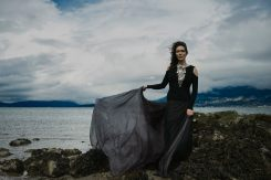 Outdoor natural light portrait of a woman on a rocky shoreline wearing a large silver breastplate necklace and long chiffon skirt billowing in the wind