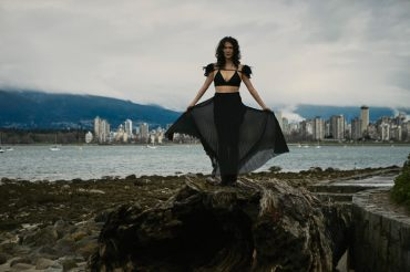 Outdoor natural light portrait of a woman holding a long pleated skirt away from her body as it blows in the wind with English Bay in the background