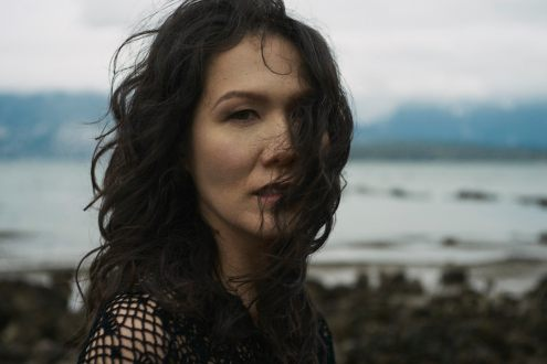 Outdoor natural light portrait of a woman standing on a rocky shoreline with moody clouds looking straight at the camera while the wind blows her curls across her face