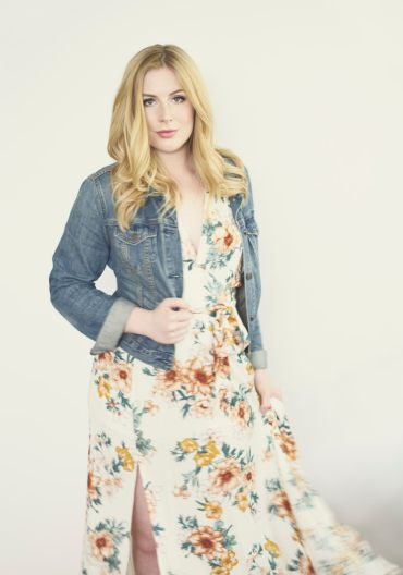 Studio portrait of a young woman in a floral dress and denim jacket looking at the camera