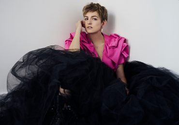 Natural light portrait portrait of a young woman wearing a structural pink crop jacket and large black tulle skirt with combat boots looking directly at the camera