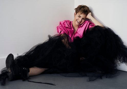Natural light portrait portrait of a young woman wearing a structural pink crop jacket and large black tulle skirt with combat boots laughing at the camera