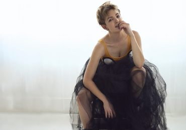 Natural light backlit portrait wearing a large tulle skirt and cartoon top looking at the camera