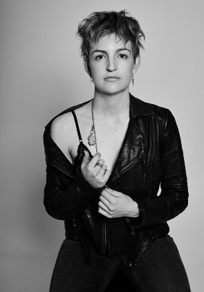 Black and white portrait of a young woman wearing a black bralette, jeans and leather biker jacket looking directly at the camera