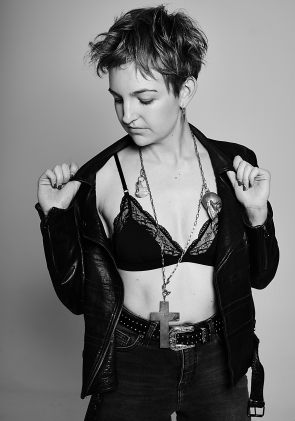 Black and white portrait of a young woman wearing a black bralette, jeans and leather biker jacket
