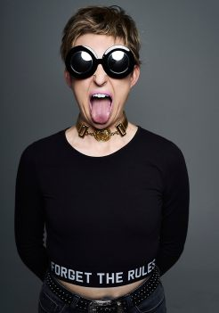 Studio portrait of a young woman with blonde hair wearing large black sunglasses and mauve lipstick sticking her tongue out at the camera