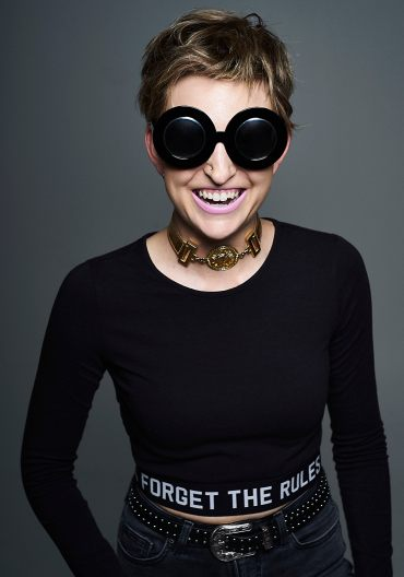 Studio portrait of a young woman with blonde hair wearing large black sunglasses and mauve lipstick laughing at the camera
