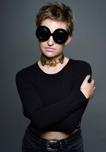 Studio portrait of a young woman with blonde hair wearing large black sunglasses and mauve lipstick