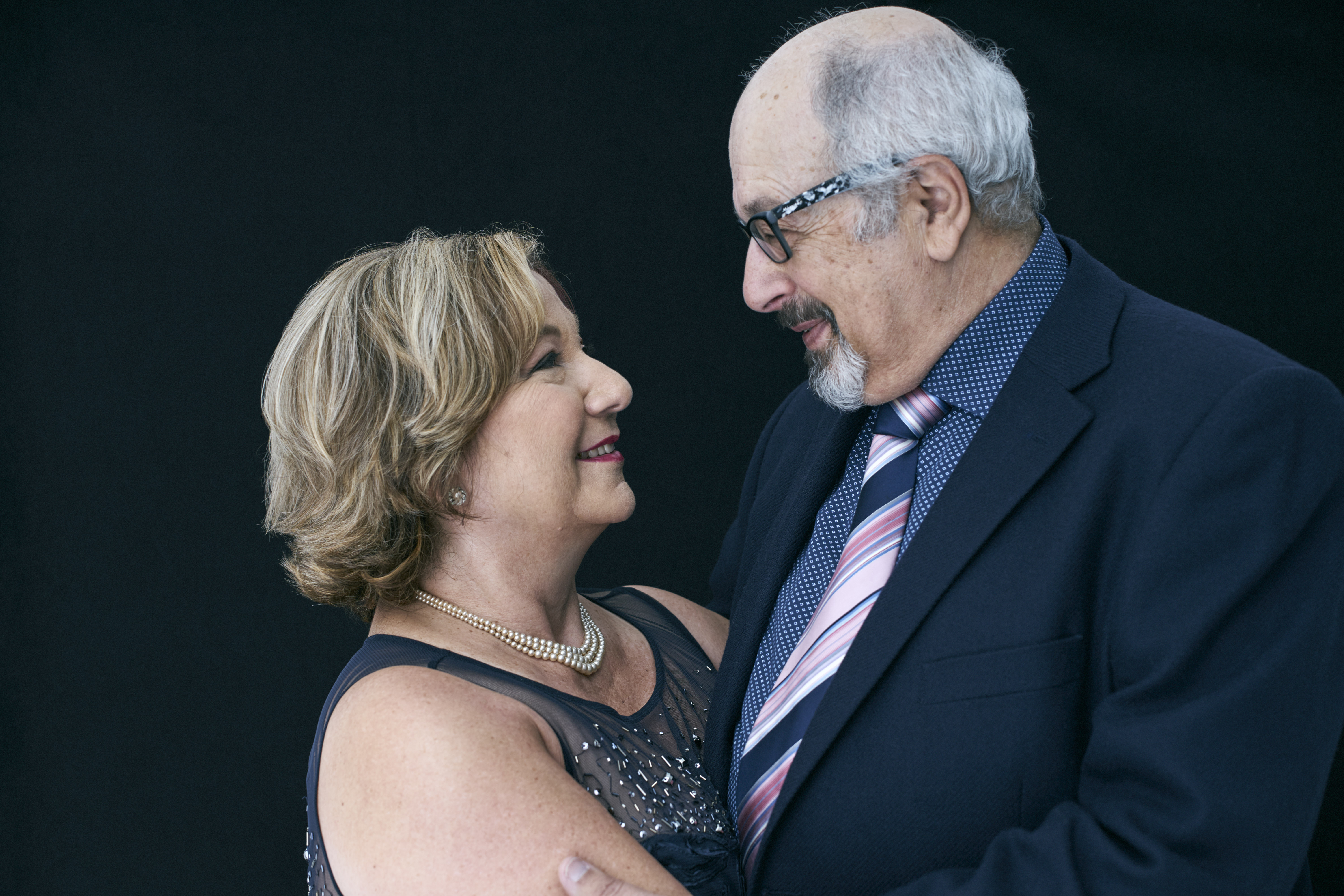 Studio portrait of an older couple both in smart clothing hugging and smiling at each other