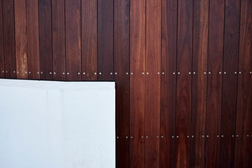 Abstract image of wood panelling with a white concrete insert in the bottom left corner