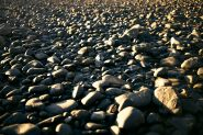 Sunset light cast across river rocks on the beach at Ngati Toa Domain in Mana Wellington