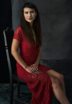 Studio portrait of a young woman wearing a red lace dress sitting on an ornate wooden chair smiling at the camera