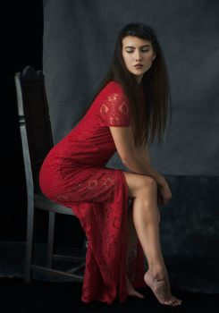 Studio portrait of a young woman wearing a red lace dress sitting on an ornate wooden chair looking away from the camera