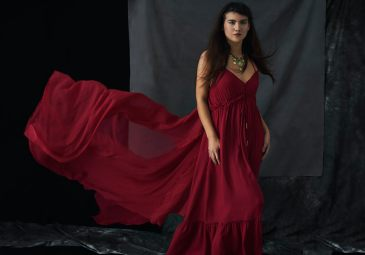Studio portrait of a young woman wearing a red boho dress and with long hair blowing away from her face