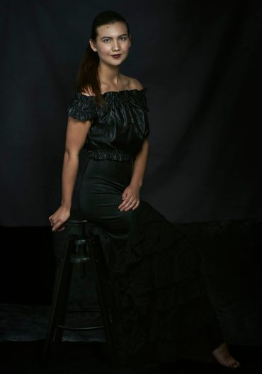 Studio portrait of a young woman with hair pulled back in a pony tail wearing a black cold shoulder top and black ruffled skirt smiling at the camera