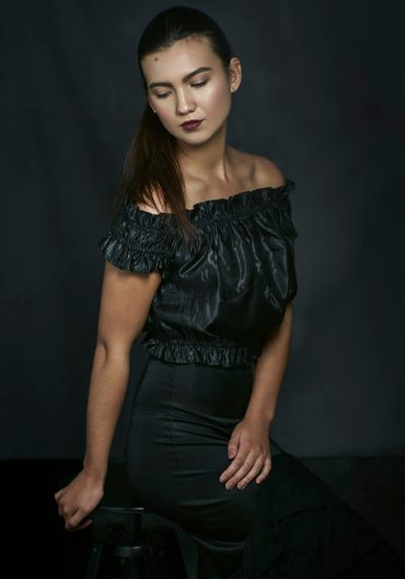Studio portrait of a young woman with hair pulled back in a pony tail wearing a black cold shoulder top and black ruffled skirt looking away from the camera