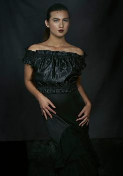 Studio portrait of a young woman with hair pulled back in a pony tail wearing a black cold shoulder top and black ruffled skirt looking at the camera