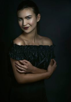 Studio portrait of a young woman with hair pulled back in a pony tail wearing a black cold shoulder top smiling at the camera