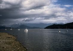 Image of rain clouds passing over mountain ranges with boats on an inlet in the foreground at Gibsons on the Sunshine Coast, BC