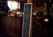 Image of the interior of Persephone Brewing Company with a log fire and menu chalkboard