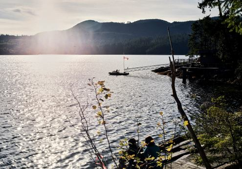 Image of a dock with deck chairs and a Canadian flag on an inlet with the sunshine streaming over the hills in Autumn at Sechelt on the Sunshine Coast, BC