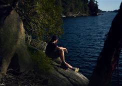 Image of a man reclining on a rock face looking over an inlet in Sechelt on the Sunshine Coast, BC