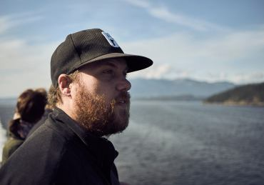 Image of a bearded man wearing a cap looking out to the mountain ranges from the ferry to Horseshoe Bay, BC