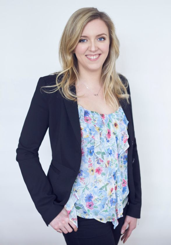 Business portrait of a young woman with blonde hair wearing a floral top and blue blazer smiling at the camera