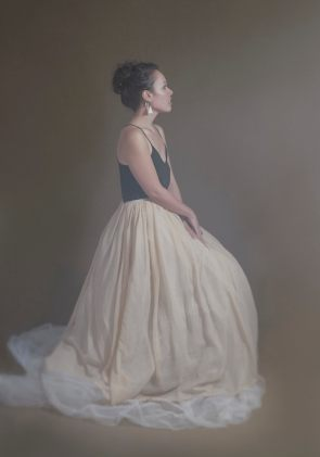 Studio portrait of a young Maori woman in a large tulle skirt posing in profile