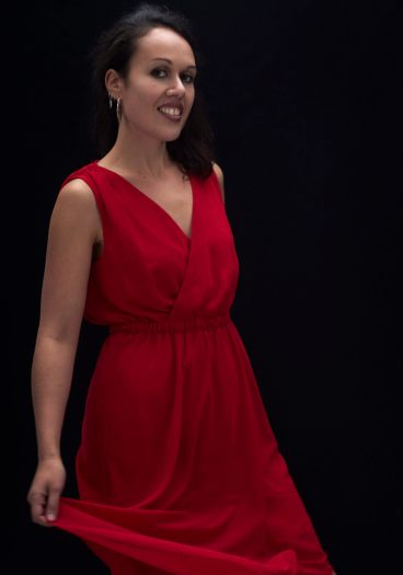 Studio portrait of a young Maori woman in a red dress twirling her skirt and smiling at the camera