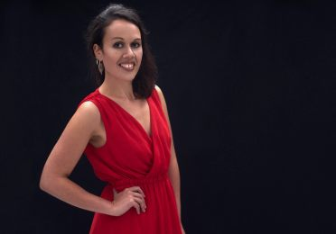 Studio portrait of a young Maori woman in a red dress smiling at the camera