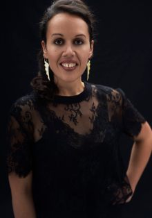 Studio portrait of a young Maori woman in a black dress and lace top smiling at the camera