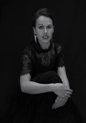 Black and white studio portrait of a young Maori woman in a black dress and lace top looking at the camera