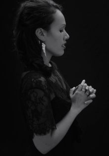 Black and white studio portrait of a young Maori woman in a black dress and lace top posing in profile