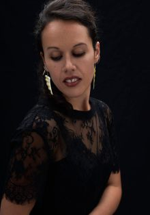 Studio portrait of a young Maori woman in a black dress and lace top looking away from the camera