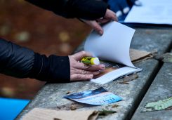 Image of a woman pasting an inspirational quote into a journal at a coaching session at an outdoor retreat
