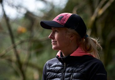 A woman in a cap and hair in a ponytail smiling as she listens to other people talking during a coaching session at an outdoor retreat