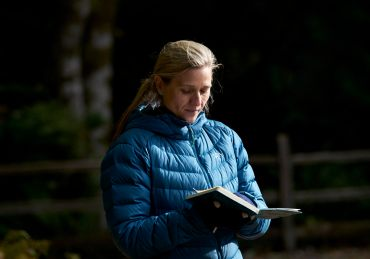 A woman in blue reading from a journal while running a coaching session at an outdoor retreat