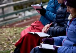 Women wrapped up in blankets and wearing winter jackets writing in journals during a coaching session at an outdoor retreat