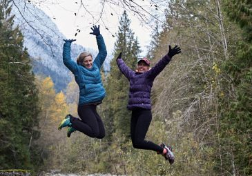 Two women in winter athletic apparel jumping in the air with a look of joy on their faces